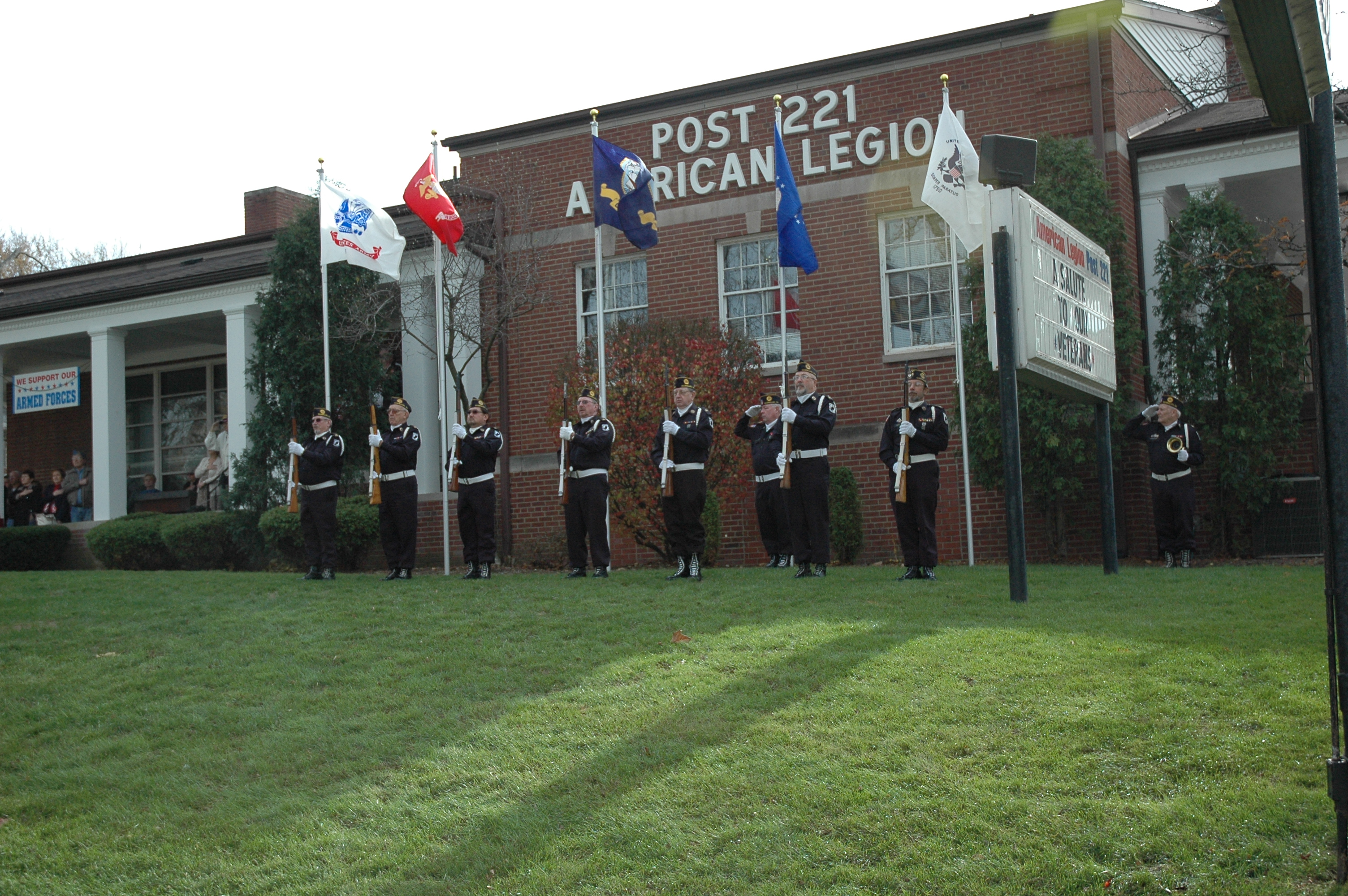 In front of the red-brick post building, seven members of the Color Guard stand in front of the legion's new five service flags.